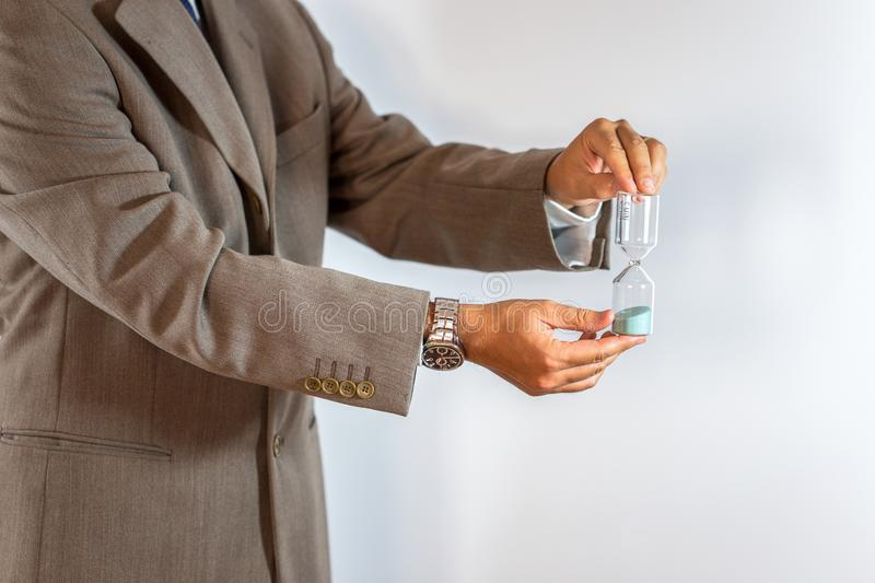 Businessman holding an hourglass stock images