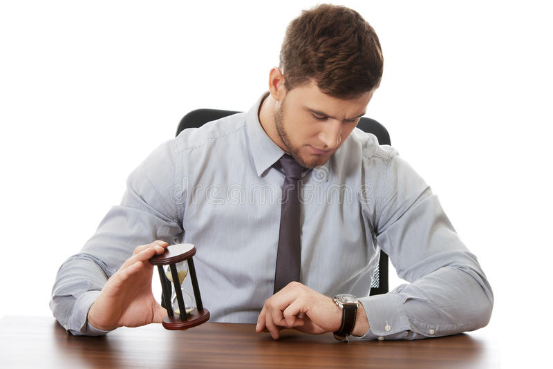 Businessman holding hourglass. Businessman holding hourglass an checking time on his watch stock images
