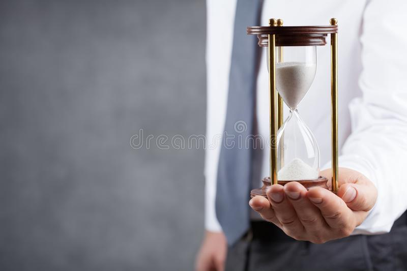Businessman holding hourglass in his hand. Deadline and time management concept. royalty free stock photos