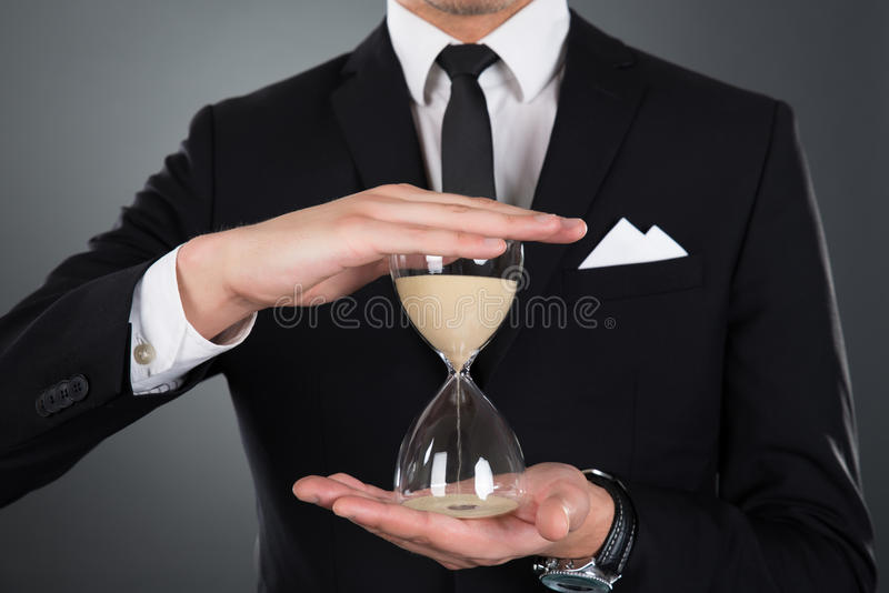 Businessman holding hourglass. Midsection of businessman holding hourglass against gray background stock photography