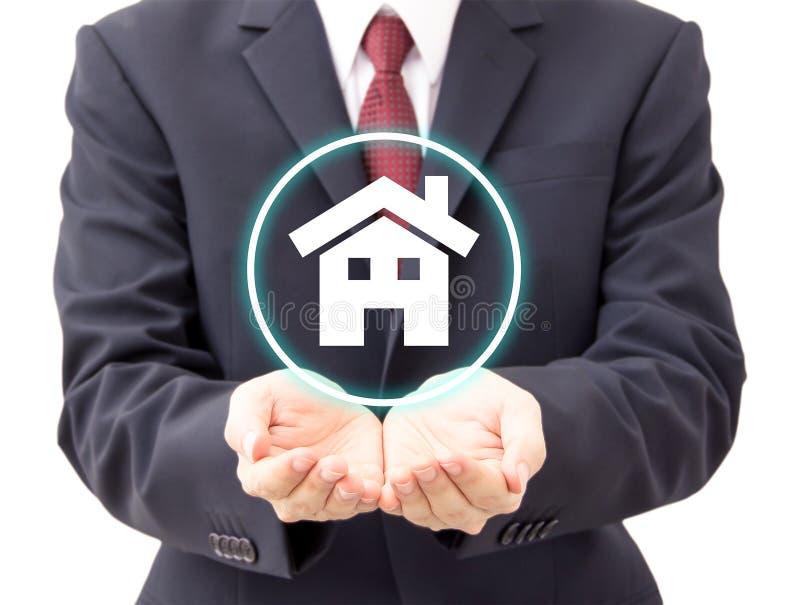 Businessman holding house icon stock photo