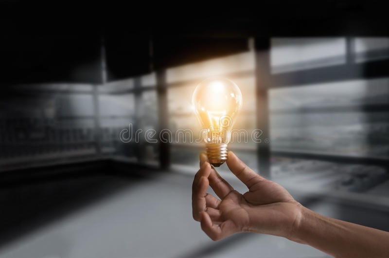 Businessman holding illuminated light bulb concept for idea, innovation and creativity inspiration concept ideas stock photo