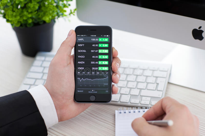 Businessman holding iPhone 6 with application Stocks of Apple. Alushta, Russia - November 3, 2014: Businessman holding a iPhone 6 Space Gray with application royalty free stock photos
