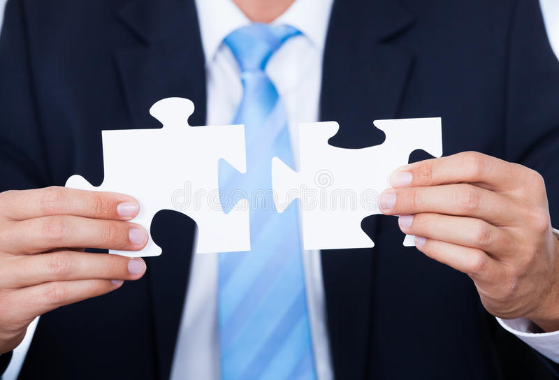 Businessman holding jigsaw puzzle royalty free stock images