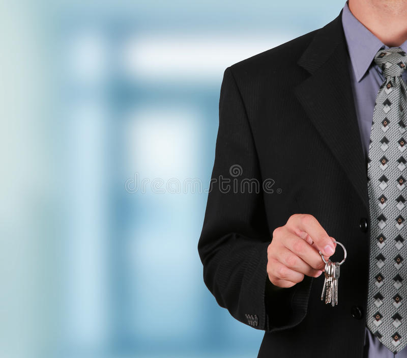 Businessman holding key in his hand to hand it over royalty free stock images