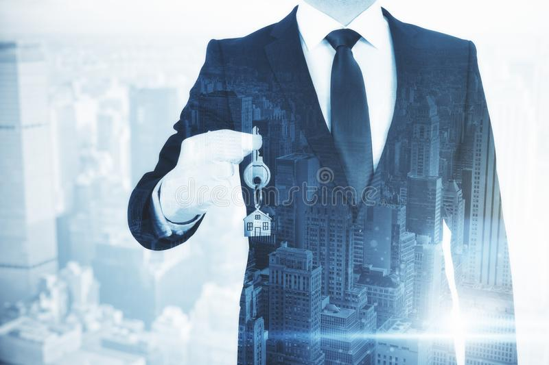 Real estate and housing concept. Businessman holding key with house keychain on abstract city background. Real estate and housing concept. Double exposure royalty free stock photography