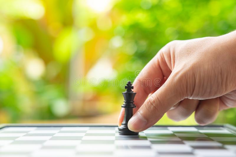 Businessman holding a King Chess is placed on a chessboard.using as background business concept and Strategy concept with copy stock photo