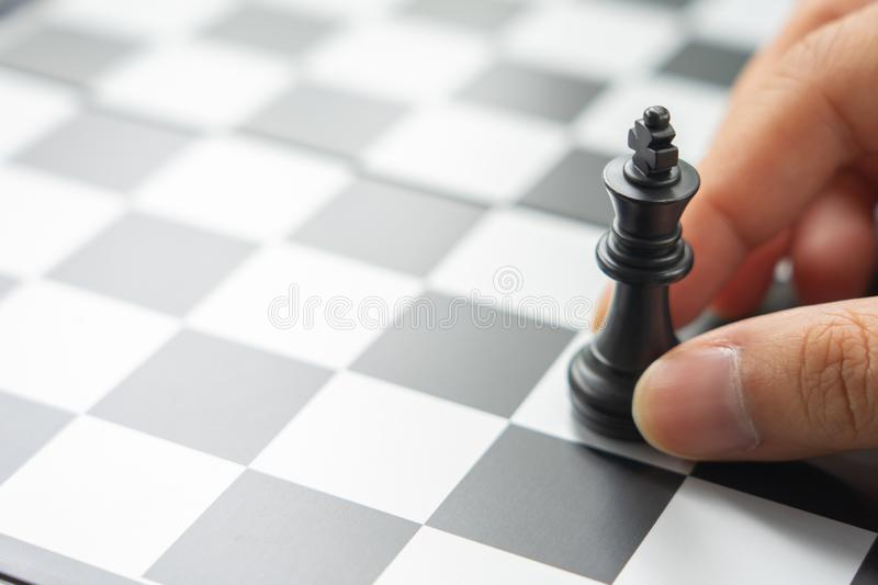 Businessman holding a King Chess is placed on a chessboard.using as background business concept and Strategy concept with copy royalty free stock image