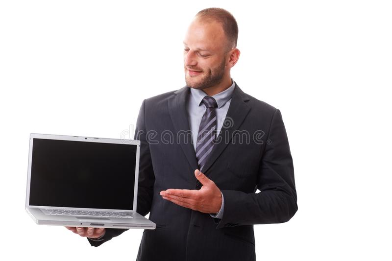 Businessman holding laptop with blank screen. Showing laptop with other hand, smiling stock image