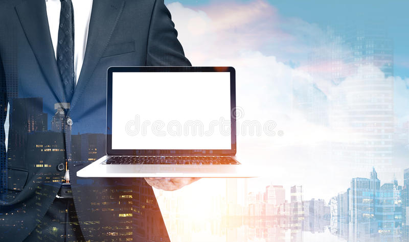 Businessman holding laptop, city. Close up of an unrecognizable businessman holding a laptop with a blank screen and standing against a cityscape background royalty free stock image