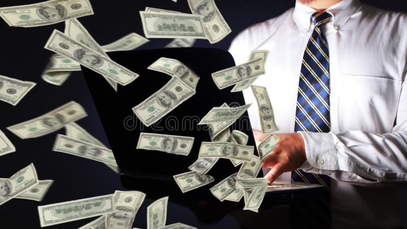 Businessman Holding Laptop with Rain of Money royalty free stock photography
