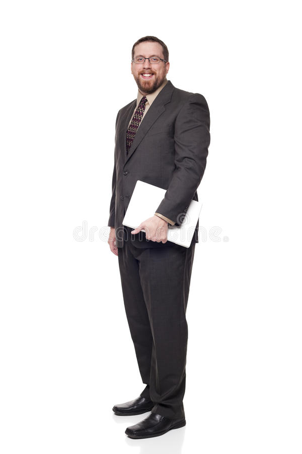 Businessman holding a laptop while standing. Isolated full length studio shot of the side view of a businessman carrying a laptop and looking at the camera royalty free stock photos
