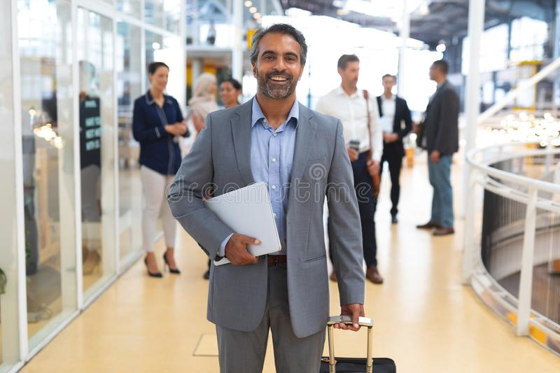 Businessman holding laptop and trolley bag and looking at camera in a modern office royalty free stock photo