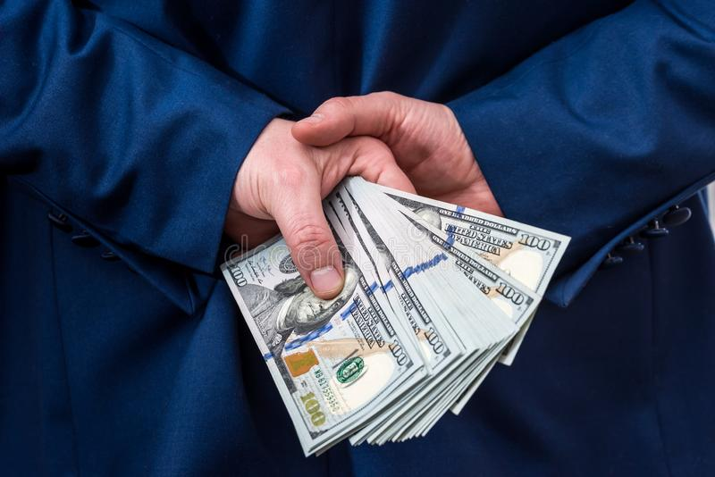 Businessman holding large amount of dollar. And give you stock photo