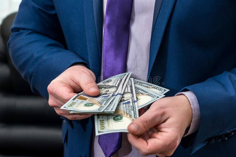 Businessman holding large amount of dollar and give you.  stock photography