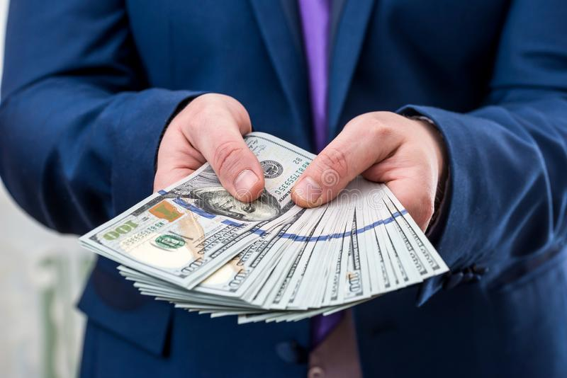 Businessman holding large amount of dollar and give you.  royalty free stock photos