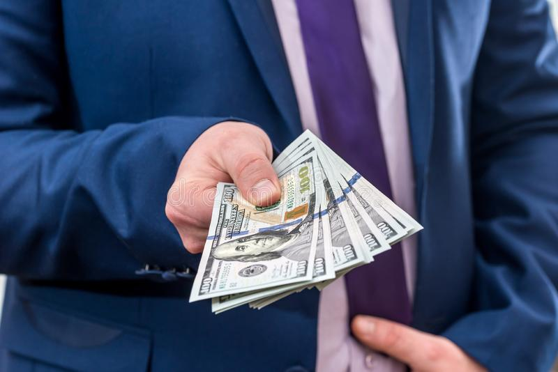 Businessman holding large amount of dollar and give you. Businessman holding large amount of dollar and give you stock photography