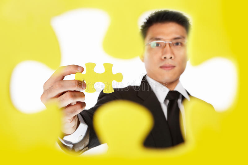 Businessman holding the last piece of puzzle. Asian businessman showing the last piece of puzzle, over white background stock images