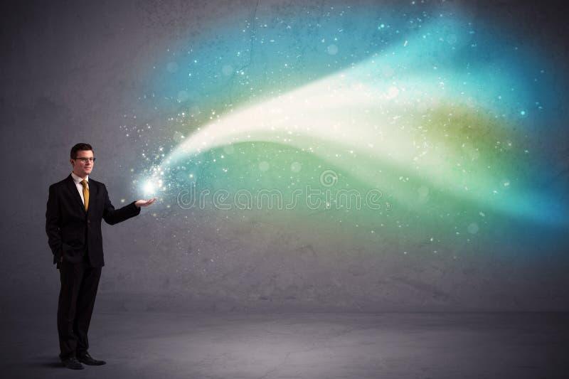 Businessman holding light. Caucasian businessman holding aurora borealis kind of stria of light stock photo