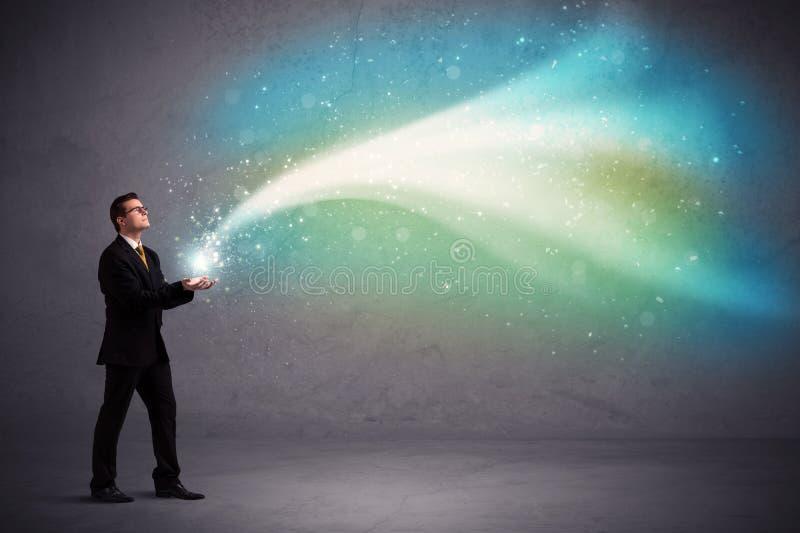 Businessman holding light. Caucasian businessman holding aurora borealis kind of stria of light stock image