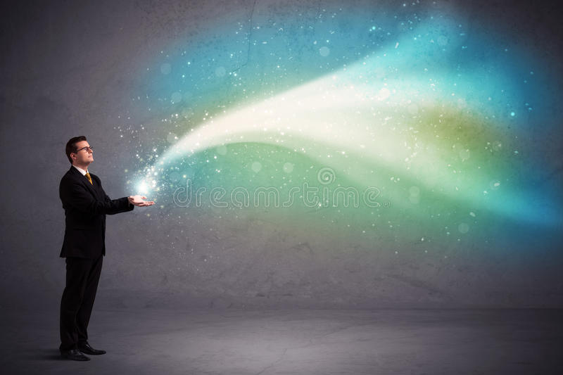 Businessman holding light. Caucasian businessman holding aurora borealis kind of stria of light stock photography