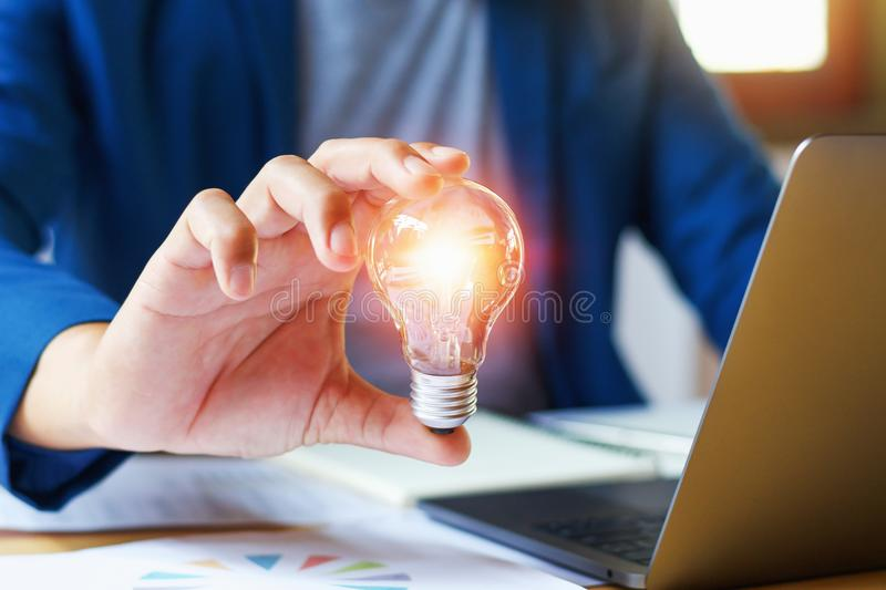 businessman holding lightbulb in office. creative idea for saving energy. concept finance and accounting royalty free stock photography