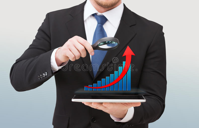Businessman holding magnifier over tablet pc stock photography