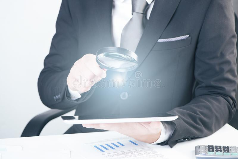 Businessman holding magnifying glass and digital tablet stock photos