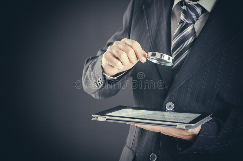 Businessman holding magnifying glass and digital tablet on dark background, searching and examining concept royalty free stock photo
