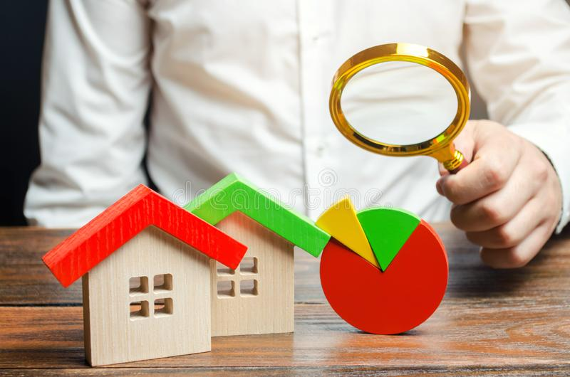 Businessman holding a magnifying glass over a pie chart and a wooden houses. Concept analysis of the real estate market. Mortgage stock photography