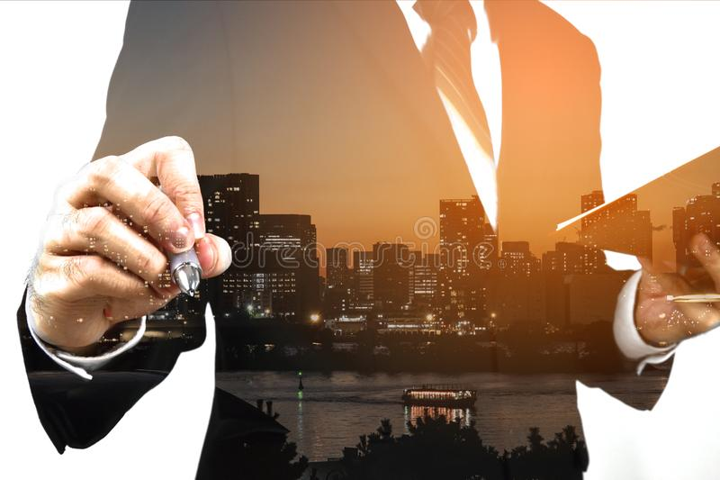 Businessman holding memo and ready to write down. Double exposure, panoramic view contemporary megalopolis background, orange sun. Businessman holding memo and stock photos