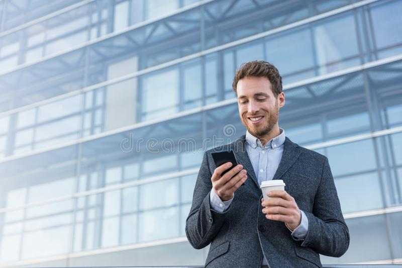 Businessman holding mobile cell phone using app texting sms message wearing suit. Young urban professional man using smartphone at royalty free stock photo