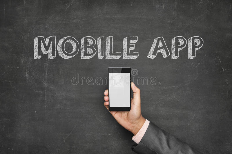 Businessman Holding Mobile Phone Under Text On Blackboard stock photography