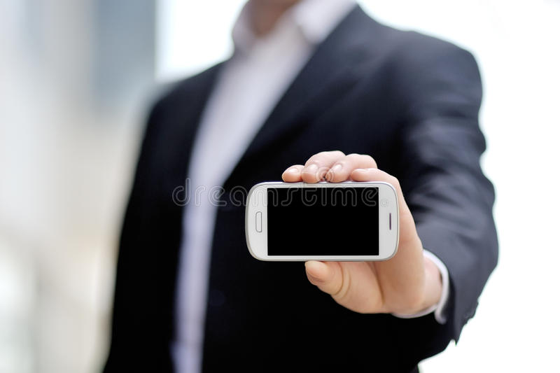 Businessman holding mobile smart phone in hand royalty free stock image