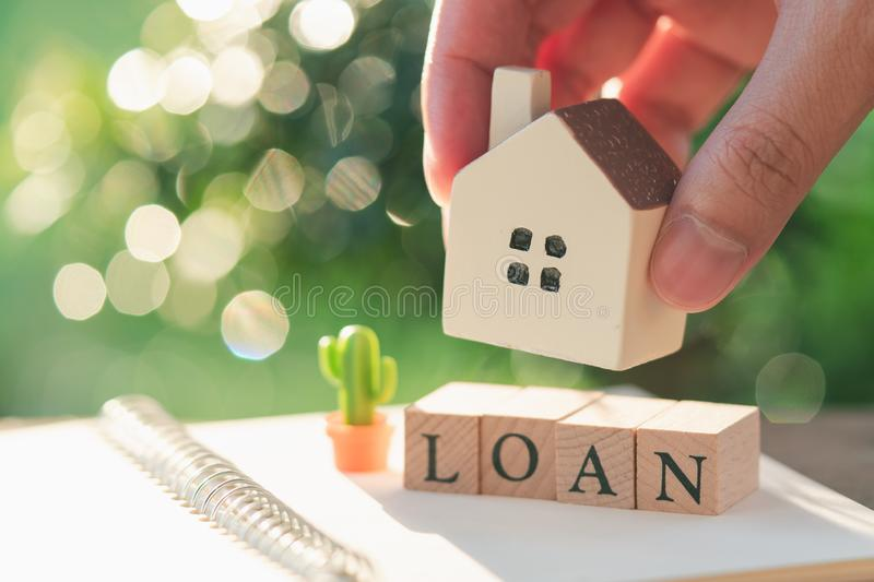 Businessman holding a model house model is placed on wood word LOAN.using as background business concept and real estate concept stock photography