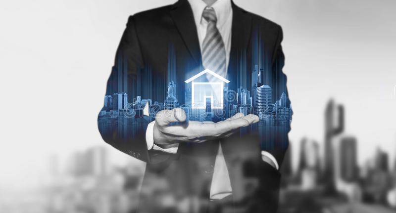 Businessman holding modern buildings hologram, and home icon. Real estate business, building technology and smart home concept. S stock photography
