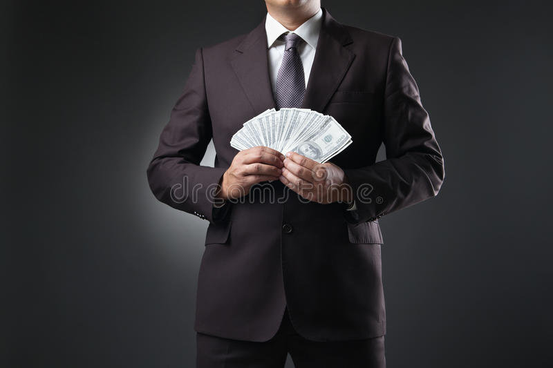 Businessman holding money in hands on dark. Businessman in suit holding money in hands on dark background royalty free stock image