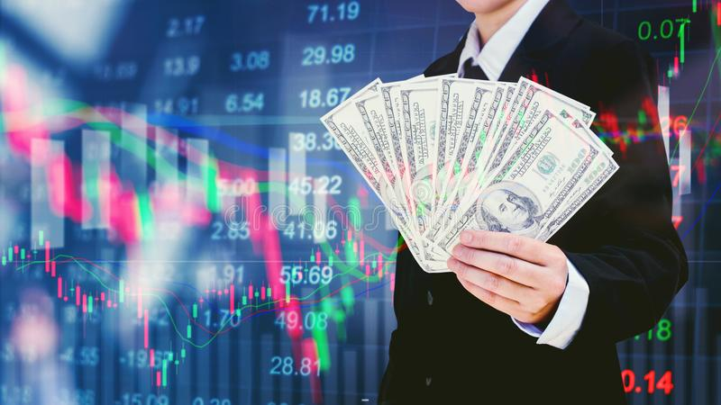 Businessman Holding money US dollar bills on digital stock market financial exchange information and Trading graph background.  stock photography