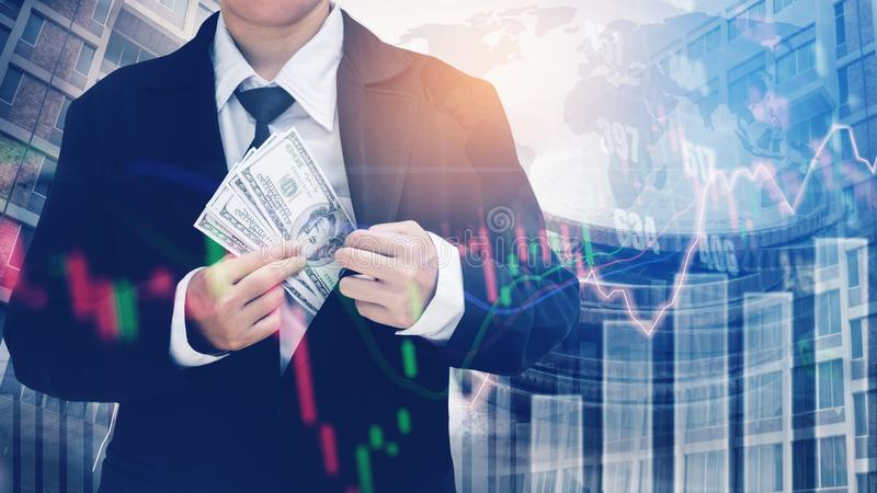 Businessman Holding money US dollar bills on digital stock market financial exchange and Trading graph Double exposure city on th. E background stock image