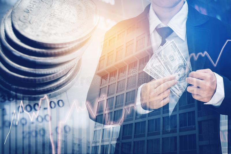 Businessman Holding money US dollar bills on digital stock market financial exchange and Trading graph Double exposure city on th. E background royalty free stock photography