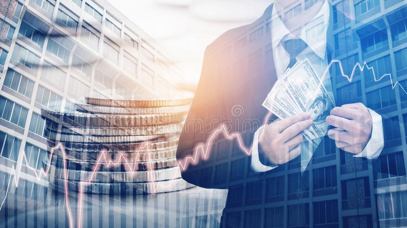 Businessman Holding money US dollar bills on digital stock market financial exchange and Trading graph Double exposure city on th. E background royalty free stock image