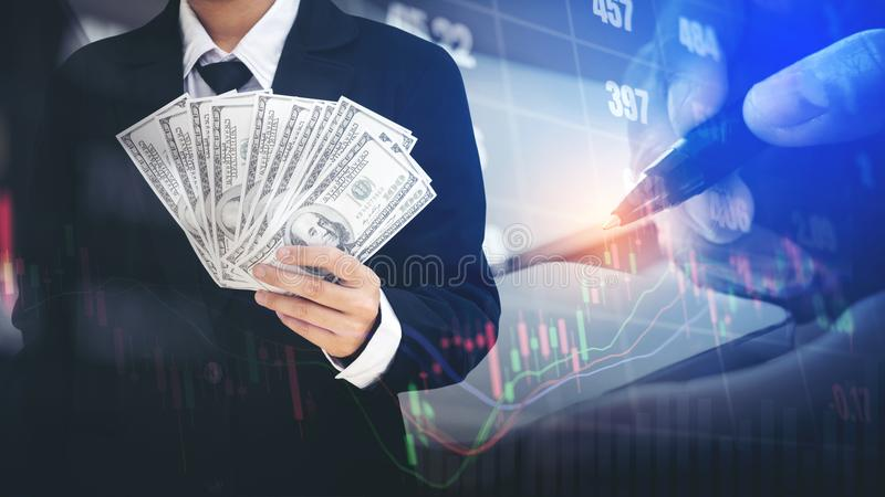 Businessman Holding money US dollar bills on digital stock market financial exchange information and Trading graph background.  royalty free stock images