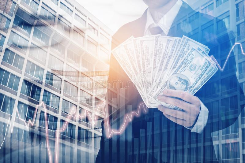 Businessman Holding money US dollar bills on digital stock market financial exchange and Trading graph Double exposure city on th. E background royalty free stock images