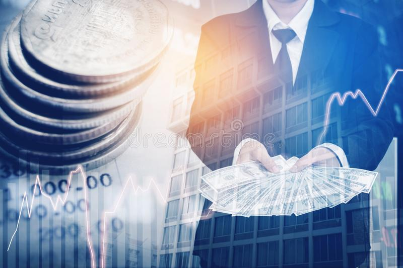 Businessman Holding money US dollar bills on digital stock market financial exchange and Trading graph Double exposure city on th. E background stock photography