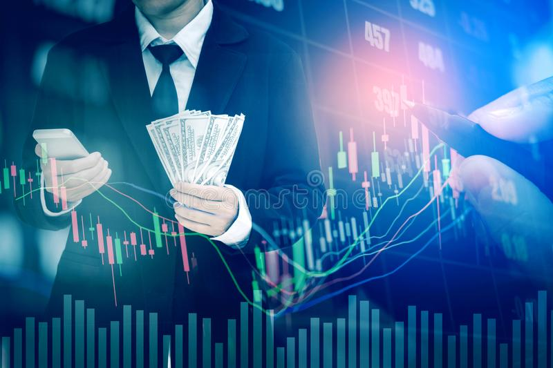 Businessman Holding money US dollar bills on digital stock market financial exchange information and Trading graph background.  royalty free stock photography