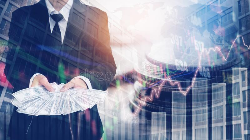 Businessman Holding money US dollar bills on digital stock market financial exchange and Trading graph Double exposure city on th. E background royalty free stock photo