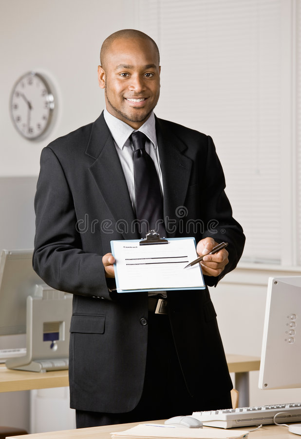 Businessman holding out contract. Confident businessman holding out contract for customer to sign stock photos