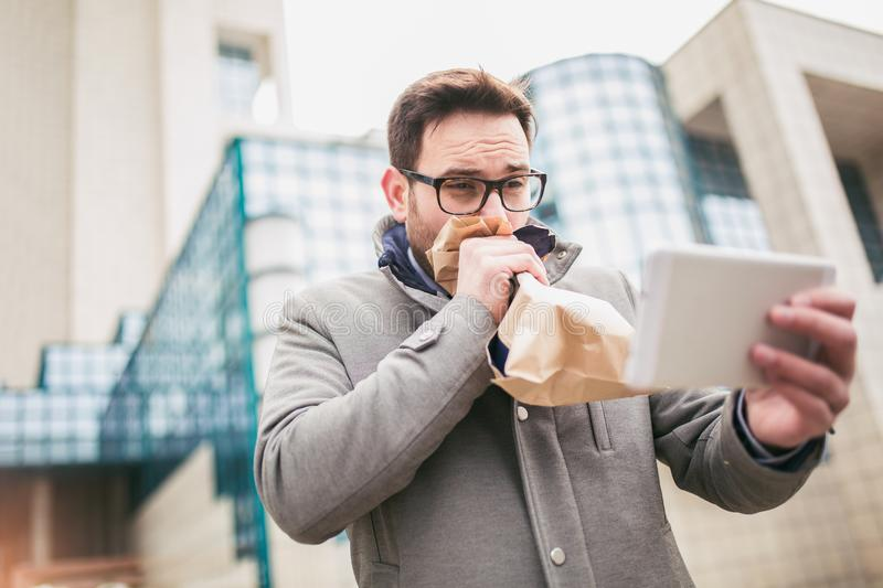Businessman holding paper bag over mouth as if having a panic attack royalty free stock image