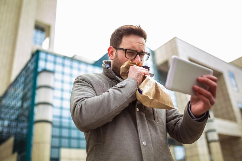 Businessman holding paper bag over mouth as if having a panic attack. And looking in digital tablet stock images