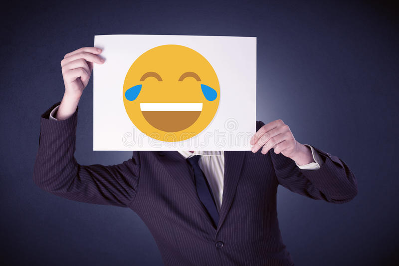 Businessman holding paper with laughing emoticon. Young businessman hiding behind a laughing emoticon on cardboard stock image
